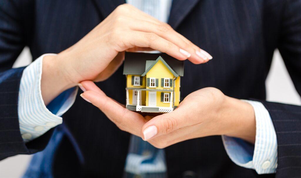 Frau im Anzug hält Haus in der Hand