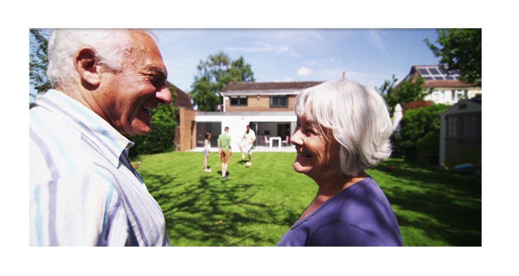 Oma Opa im Garten mit EFH im Hintergrund